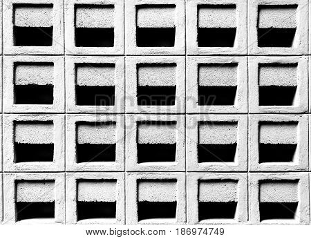 Ventilation cement block wall pattern in the under tone with black and white color selective focus.