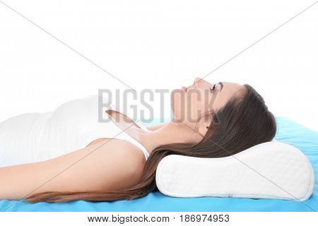 Young woman lying on bed with orthopedic pillow against white background. Healthy posture concept