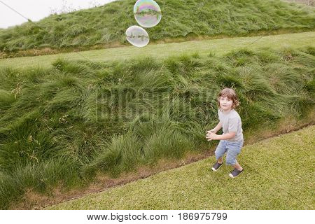 Caucasian boy looking at floating bubbles