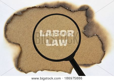 Text Labor Law written under a magnifier on a burnt paper poster