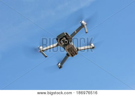 Close up of small drone in blue sky who capturing the video