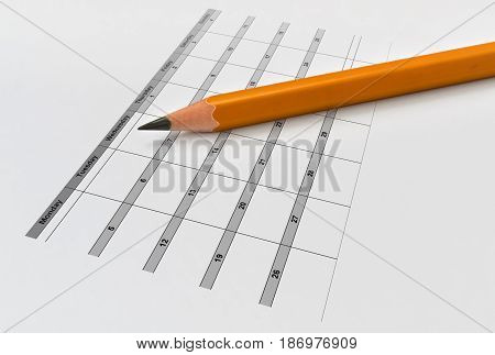 Closeup of a yellow pencil and calendar on bright background