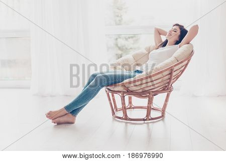Weekends Finally! Relaxed Brunette Girl Is Sitting On Modern Chair Near The Window In Light Cozy Roo