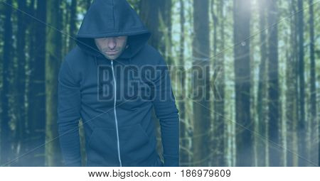 Digital composite of Criminal in hood in front of forest