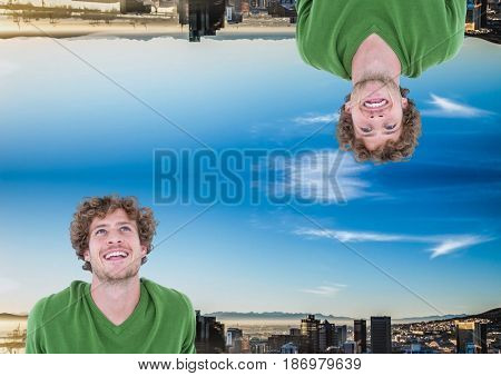 Digital composite of up side down city. green jumper and happy men. Blue sky city