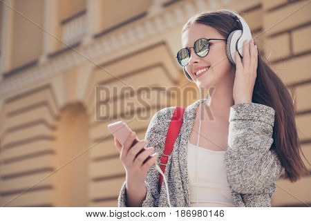 Chilling On The Sun. Young Attractive Girl Is Listening To The Music Outdoors On Hr Pda, Wearing Sun