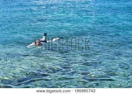Woman swimming in sea trasparent water in Tremiti islands Italy