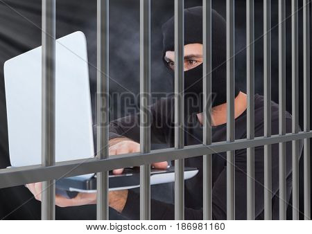 Digital composite of Criminal in balaclava with laptop behind prison bars