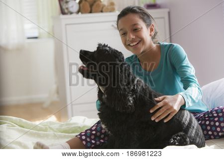 Hispanic girl petting dog on bed