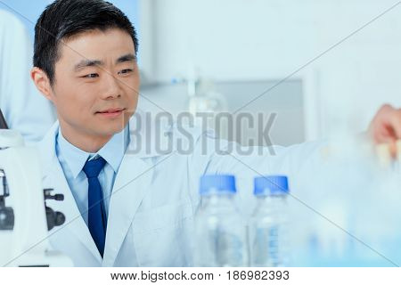 Asian Scientist In White Coat Working In Chemical Laboratory