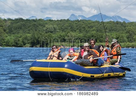 BYSTRAYA RIVER KAMCHATKA PENINSULA RUSSIA - JULY 13 2016: Summer rafting on Kamchatka - group of tourists and travelers floating on calm river on raft on background of green forest and mountains.