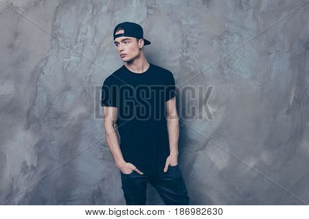 Young Serious Man In Cap And Black Outfit Is On The Grey Background, His Hands Are In Pockets