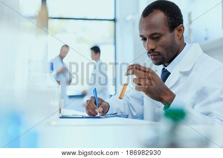 African American Scientist In White Coat Holding And Examining Test Tube With Reagent, Laboratory Re