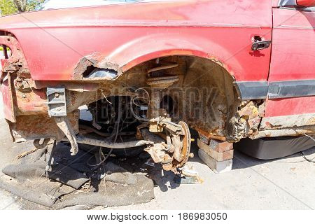 The crumpled car after a serious accident is covered with rust and stands on the street