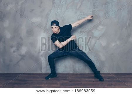 Portrait Of A Young Handsome Dancer Making His Moves. Guy Is Wearing Black T Shirt And Jeans And Cap
