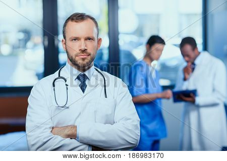 Portrait Of Confident Doctor With Stethoscope With Colleagues Behind In Clinic