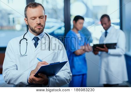 Portrait Of Confident Doctor Writing In Folder In Clinic With Colleagues Behind