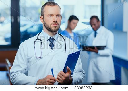 Portrait Of Confident Doctor Holding Folder In Clinic With Colleagues Behind