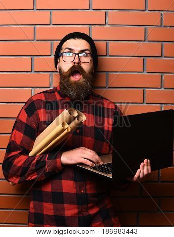 Bearded man long beard. Brutal caucasian surprised unshaven hipster holding laptop and craft paper rolls in red black checkered shirt with hat and glasses on brown brick wall studio background