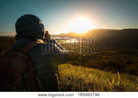 Hiker taking photo of the valley at sunrise