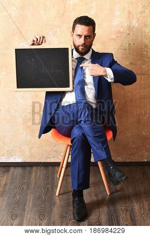 serious businessman in blue suit holding a blackboard