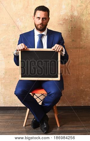 businessman or serious man holding a blackboard copy space