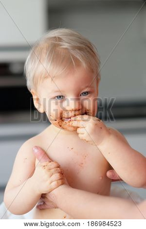 Adorable one year old baby boy playing with food. Toddler child eating fruit. Dirty messy face of happy kid.