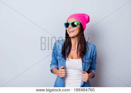 Portrait Of A Playful Young Latin Girl In A Casual Clothes And Bright Green Sunglasses, Pink Hat Sta