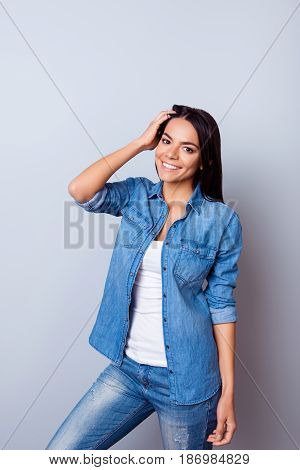 Young Successful Latin Young Woman Is Standing On Light Blue Background And Fixing Her Hair