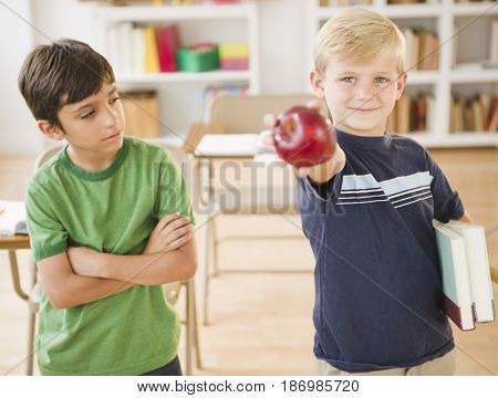 Boy in classroom holding out apple