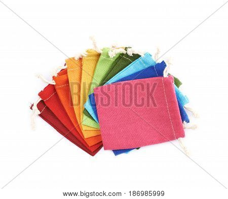 Twisted pile of the colorful cloth gift bags isolated over the white background