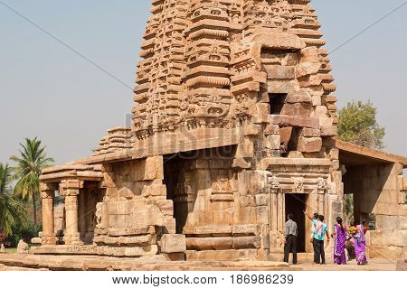 PATTADAKAL, INDIA - FEB 9, 2017: Group of tourists watching the towers of ancient Hindu temple on February 9, 2017. UNESCO World Heritage site with stone carved structures of 7th and 8th-century