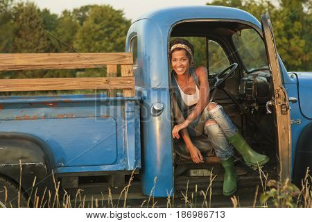 Mixed race woman sitting in old-fashioned truck