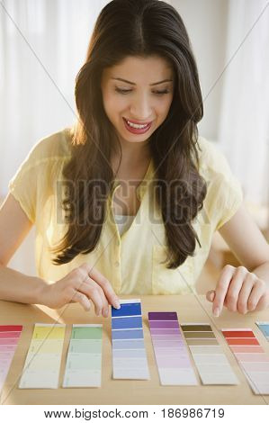 Mixed race woman looking at paint swatches