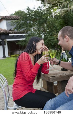 Hispanic couple drinking together outdoors