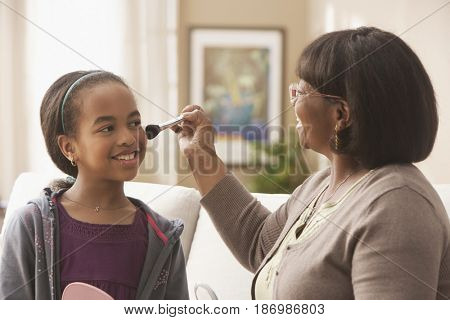 African American grandmother putting makeup on granddaughter