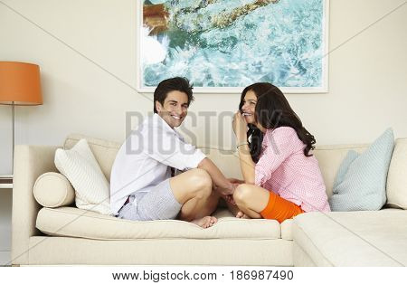 Smiling couple sitting on sofa together