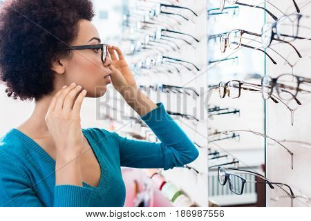 Black woman trying on glasses she wants to buy in optician store