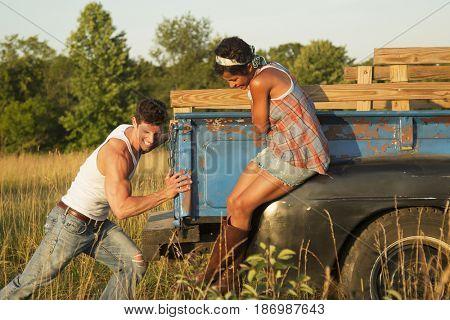 Woman watching boyfriend pushing truck