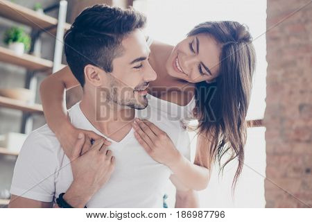 Beautiful Couple Of Young Lovers Are Hugging Indoors At Home, Looking At Each Other With Love And Te
