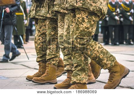 Soldiers in camouflage military uniform in march position, walking