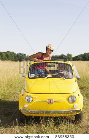 Woman standing in car sun roof in field