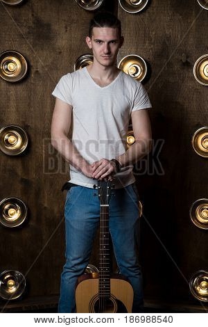Guitarist, Music. A Young Man Stands With An Acoustic Guitar In The Background With The Lights Behin