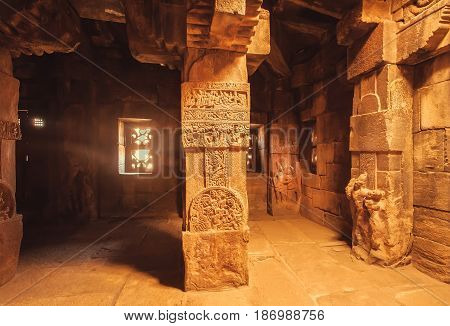 Dark room with artistic columns in Hindu temple in Pattadakal, India. UNESCO World Heritage site with stone carved temples of 7th and 8th-century