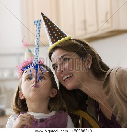 Caucasian mother and daughter at birthday party