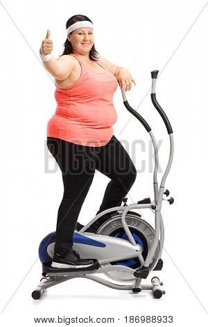 Full length portrait of an overweight woman exercising on a cross trainer machine and making a thumb up sign isolated on white background