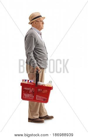 Full length profile shot of an elderly man with a shopping basket waiting in line isolated on white background