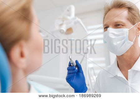 Friendly specialist. Caring competent neat doctor protecting his patient and himself from infections while using professional equipment for treating young woman