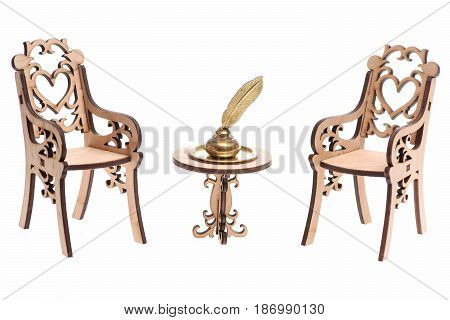 Feather pen into inkwell on golden tray on decorative engraved wooden table and chairs isolated on white background copy space
