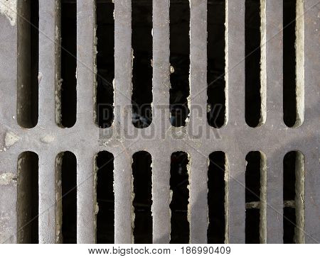 Sewer drain is covered with iron grating. Inside the pit water is visible. Closeup.